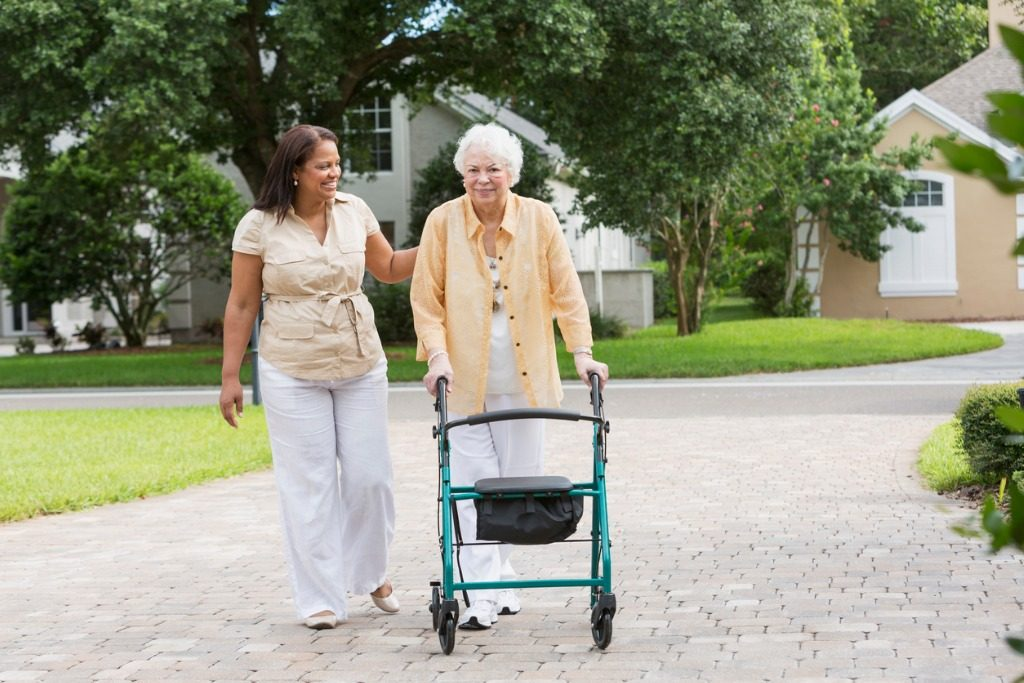 Home health aide accompanying a senior women on a walk.